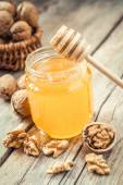 Honey in glass jar, walnut in basket and wooden dipper — Stock Photo