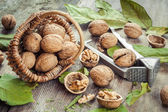 Walnuts, nutcracker and basket on old wooden table — Stockfoto