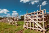 Wooden rustic fence, blue sky and village landscape — Stock Photo