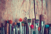 Row of artist paintbrushes closeup on old wooden table, retro st — Stock Photo