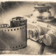 Old photo film roll and retro camera on desk. — Stock Photo #58447059