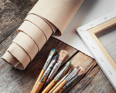 Artist canvas in roll, canvas stretcher and paintbrushes — Stock Photo