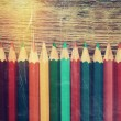 Row of colored drawing pencils closeup on old desk. Vintage styl — Stock Photo #58712203