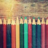 Row of colored drawing pencils closeup on old desk. Vintage styl — Zdjęcie stockowe