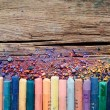 Pastel crayons and pigment dust on rustic wooden background. — Stock Photo #59397407