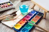 Set of watercolor paints, art brushes, glass of water and easel  — Stock Photo