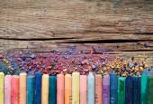 Pastel crayons and pigment dust on rustic wooden background. — Stock Photo