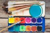 Set of watercolor paints, art brushes and glass of water on old  — Stock Photo