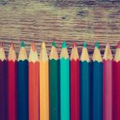 Row of colored drawing pencils closeup on old desk.  — Stock Photo