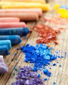 Collection of rainbow colored pastel crayons with crushed chalk. — Stock Photo