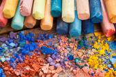 Collection of rainbow colored pastel crayons with crushed chalk  — Stock Photo