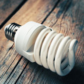 Close up of energy saving light bulb on wooden desk. Vintage sty — Stock Photo