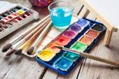 Box of watercolor paints, art brushes, glass of water and easel  — Stock Photo
