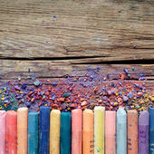 Artistic pastel crayons and pigment dust on rustic wooden backgr — Stock Photo