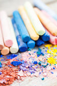 Pile of crushed chalk closeup and rainbow colored pastel crayons — Stock Photo