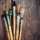 Bunch of old artist paintbrushes on wooden rustic table — Stock Photo