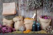 Healing herbs in hessian bags near wooden wall, herbal medicine. — Stock Photo