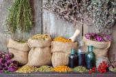 Healing herbs in hessian bags and bottles of essential oil near — Stock Photo