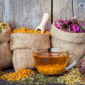 Healing herbs in hessian bags and healthy tea cup on rustic wood — Stockfoto