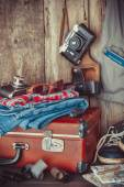 Old travel suitcase, sneakers, clothing, sunglasses, maps, films — Stock Photo