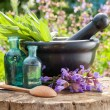 Black mortar with sage herbs, glass bottles of essential oil out — Stock Photo #67178671