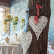 Two wicker hearts hanging on tree in wedding hall. — Stock Photo #70796115