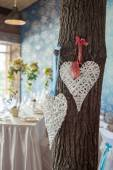 Two wicker hearts hanging on tree in wedding hall. — Stock Photo