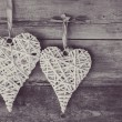 Two wicker hearts hanging on wooden background. — 图库照片 #72688283