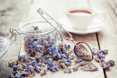 Healthy forget me not tea in glass jar, strainer and tea cup on — Stock Photo