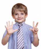 Smiling boy shows eight fingers on a white background — Stock Photo