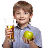 Smiling caucasian boy with a glass of juice and apple — Stock Photo