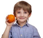 Beautiful caucasian boy holding a ripe orange. — Stock Photo