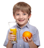 Cute caucasian boy holding a glass of orange juice and orange — Stock Photo