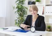 Business woman, at the table, shows the clock and smiling — Stock Photo