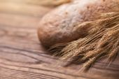 Wheat and bread on wooden table, shallow DOF — Stock Photo