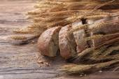 Bread and wheat on wooden table, shallow DOF — Stock Photo