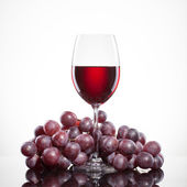 Glass of red wine and grape isolated on white — Stock Photo