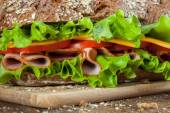Sandwich on the wooden table — Stock Photo