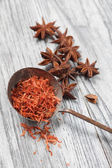Saffron in spoon with anise on wooden background — Stock Photo