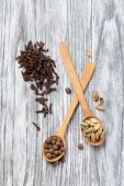 Nutmeg, clove and allspice in old spoon on wooden table — Stock Photo