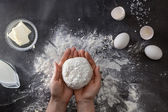 Woman's hands knead dough on table with flour — Stock Photo