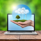 Wind turbines with tree in female hand in laptop — Stock Photo