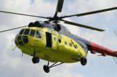 The yellow MI-8 helicopter flies against clouds with an open doo — Foto de Stock