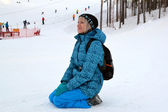 The woman in winter clothes sits on snow against the ski slope. — Stock Photo