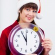 Blue-eyed beautiful girl in santa hat with clock — Stock Photo #59468765