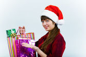 Young woman in santa hat with holiday shopping — Stock Photo