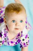 Baby girl in a dress creeps on the blue coverlet — Stock Photo