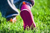 Athletic feet on grass — Zdjęcie stockowe