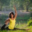 Woman performs yoga exercises and Pilates in nature — Stock Photo #56159263