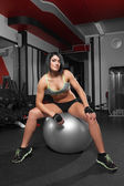 Athletic woman sitting on a gym ball — Foto de Stock
